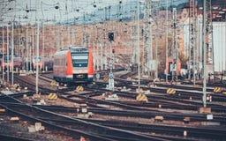 Σιδηροδρομικός σταθμός με τη σύγχρονη κόκκινη αμαξοστοιχία περιφερειακού σιδηροδρόμου στο ηλιοβασίλεμα Στοκ Φωτογραφία