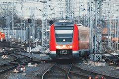 Σιδηροδρομικός σταθμός με τη σύγχρονη κόκκινη αμαξοστοιχία περιφερειακού σιδηροδρόμου στο ηλιοβασίλεμα Στοκ εικόνες με δικαίωμα ελεύθερης χρήσης