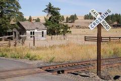 Σιδηρόδρομος που διασχίζει σημαδιών εγκαταλειμμένο το διαδρομές καλλιεργήσιμο έδαφος αγροκτημάτων σπιτιών αγροτικό Στοκ φωτογραφία με δικαίωμα ελεύθερης χρήσης