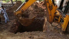 Σκάβοντας χώμα βυθοκόρων στο εργοτάξιο οικοδομής, με τη διάβαση ατόμων απόθεμα βίντεο