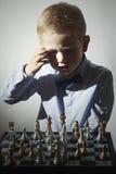 σκάκι αγοριών λίγο παιχνίδ& Έξυπνος λίγο παιδί μεγαλοφυίας Ευφυές παιχνίδι σκακιέρα Στοκ Εικόνες