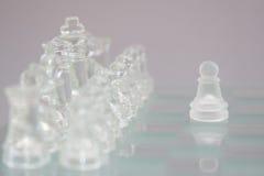 Σκάκι γυαλιού σε ένα γκρίζο υπόβαθρο στοκ εικόνες