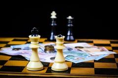 Σκάκι και χρήματα σε ένα σκοτεινό υπόβαθρο Στοκ Εικόνες