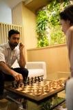 Σκάκι παιχνιδιού επιχειρηματιών με τη γυναίκα συνάδελφος Στοκ Φωτογραφία