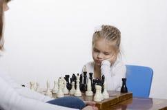 Σκάκι παιχνιδιού κοριτσιών, που σκέφτεται για την επόμενη σειρά μαθημάτων Στοκ Εικόνα