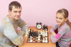 Σκάκι παιχνιδιού μπαμπάδων και κορών με το χαμόγελο και εξετασμένος το πλαίσιο στοκ φωτογραφία