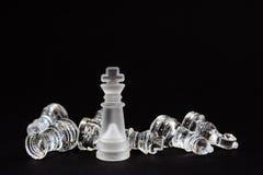 Σκάκι του γυαλιού Ο αριθμός του βασιλιά που στέκεται πέρα από τα νικημένα αντίπαλα κομμάτια ` s σε ένα μαύρο υπόβαθρο στοκ φωτογραφία