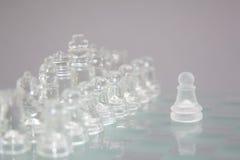 Σκάκι του γυαλιού σε ένα γκρίζο υπόβαθρο, η αρχή του παιχνιδιού στοκ φωτογραφία
