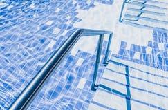 Σκάλα μετάλλων πισινών στο νερό Τα σκαλοπάτια λιμνών κλείνουν επάνω Στοκ φωτογραφία με δικαίωμα ελεύθερης χρήσης