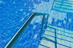 Σκάλα μετάλλων πισινών στο νερό Τα σκαλοπάτια λιμνών κλείνουν επάνω Στοκ Εικόνα