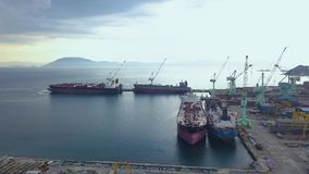 Σκάφη θάλασσας που στέκονται στο χώρο στάθμευσης κατά την άποψη κηφήνων ναυπηγείων Φορτηγό πλοίο στο εναέριο τοπίο ναυπηγείων θάλ απόθεμα βίντεο