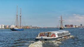 Σκάφη στον ποταμό IJ πίσω από τον κεντρικό σταθμό του Άμστερνταμ Στοκ Εικόνες