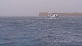 Σκάφος αναψυχής με τα πανιά τουριστών στη θυελλώδη θάλασσα στο υπόβαθρο των βράχων E απόθεμα βίντεο