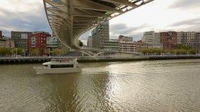 Σκάφος αναψυχής πολυτέλειας που πλέει αργά κάτω από τη γέφυρα Zubizuri στο Μπιλμπάο, Ισπανία φιλμ μικρού μήκους