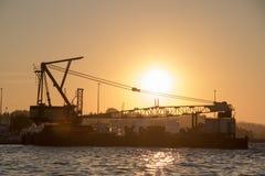 Σκάφος γερανών που ελλιμενίζει σε έναν λιμένα στο ηλιοβασίλεμα Στοκ φωτογραφία με δικαίωμα ελεύθερης χρήσης