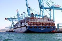 Σκάφος εμπορευματοκιβωτίων Maersk Sarat που λειτουργεί με τους γερανούς εμπορευματοκιβωτίων Στοκ εικόνα με δικαίωμα ελεύθερης χρήσης