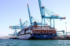Σκάφος εμπορευματοκιβωτίων Maersk Sarat που λειτουργεί με τους γερανούς εμπορευματοκιβωτίων Στοκ Φωτογραφία