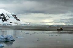 Σκάφος μεταξύ των παγόβουνων που επιπλέουν στη βάση ενός χιονισμένου βουνού στοκ εικόνα με δικαίωμα ελεύθερης χρήσης