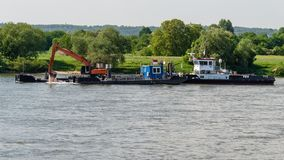 Σκάφος με τον εκσκαφέα που εμβαθύνει το κατώτατο σημείο του ποταμού στοκ φωτογραφία με δικαίωμα ελεύθερης χρήσης