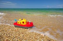 Σκάφος παιχνιδιών στη θάλασσα peble Στοκ Εικόνες