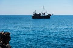 Σκάφος πειρατών που πλέει στη θάλασσα Άποψη από μια σπηλιά Στοκ Φωτογραφίες