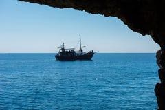 Σκάφος πειρατών που πλέει στη θάλασσα Άποψη από μια σπηλιά Στοκ Εικόνα