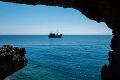 Σκάφος πειρατών που πλέει στη θάλασσα Άποψη από μια σπηλιά Στοκ Εικόνες