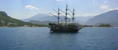Σκάφος πειρατών στη θάλασσα στα πλαίσια των βουνών Στοκ Εικόνες