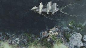 Σκάφος που πλέει κατά την εναέρια άποψη τραχιών θαλασσών σχετικά με το ηλιοβασίλεμα και το υπόβαθρο βουνών με την ελεύθερη κάμερα απόθεμα βίντεο