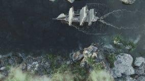 Σκάφος που πλέει κατά τη τοπ εναέρια άποψη τραχιών θαλασσών σχετικά με τη δύσκολη ακτή απόθεμα βίντεο