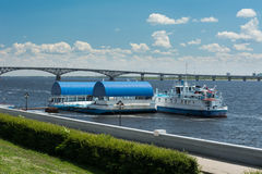 Σκάφος στην αποβάθρα ποταμών Λιμενοβραχίονας ποταμών στο υπόβαθρο της γέφυρας πέρα από τον ποταμό στοκ εικόνες