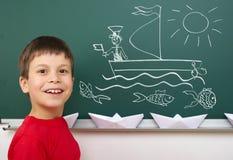 Σκάφος σχεδίων αγοριών στο σχολικό πίνακα Στοκ Φωτογραφία