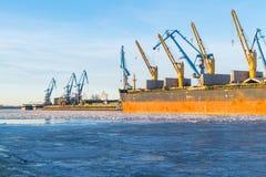 Σκάφος φορτίου φορτίου εμπορευματοκιβωτίων με τη λειτουργώντας γέφυρα γερανών στο ναυπηγείο το πρωί για το λογιστικό υπόβαθρο εισ Στοκ φωτογραφίες με δικαίωμα ελεύθερης χρήσης
