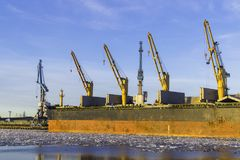 Σκάφος φορτίου φορτίου εμπορευματοκιβωτίων με τη λειτουργώντας γέφυρα γερανών στο ναυπηγείο το πρωί για το λογιστικό υπόβαθρο εισ Στοκ εικόνα με δικαίωμα ελεύθερης χρήσης