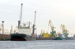 Σκάφος φορτίου φορτίου και εμπορευματοκιβώτιο φορτίου που λειτουργεί με το γερανό στην περιοχή λιμένων, λογιστική εισαγωγή-εξαγωγ Στοκ εικόνες με δικαίωμα ελεύθερης χρήσης