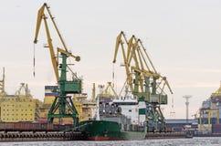 Σκάφος φορτίου φορτίου και εμπορευματοκιβώτιο φορτίου που λειτουργεί με το γερανό στην περιοχή λιμένων, λογιστική εισαγωγή-εξαγωγ Στοκ Φωτογραφία