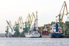 Σκάφος φορτίου φορτίου και εμπορευματοκιβώτιο φορτίου που λειτουργεί με το γερανό στην περιοχή λιμένων, λογιστική εισαγωγή-εξαγωγ Στοκ φωτογραφία με δικαίωμα ελεύθερης χρήσης