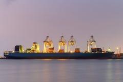 Σκάφος φορτίου φορτίου εμπορευματοκιβωτίων με την εξαγωγή εργασίας στο λυκόφως Στοκ Εικόνα