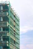 Σκάλα και υλικά σκαλωσιάς σε ένα εργοτάξιο οικοδομής, που καλύπτεται με το πλέγμα στο υπόβαθρο ουρανού. Στοκ Φωτογραφία