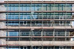 Σκάλα και υλικά σκαλωσιάς σε ένα εργοτάξιο οικοδομής, που καλύπτεται με το πλέγμα. Στοκ Εικόνα