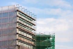 Σκάλα και υλικά σκαλωσιάς σε ένα εργοτάξιο οικοδομής, που καλύπτεται με το πλέγμα στο υπόβαθρο ουρανού. Στοκ εικόνες με δικαίωμα ελεύθερης χρήσης