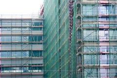 Σκάλα και υλικά σκαλωσιάς σε ένα εργοτάξιο οικοδομής, που καλύπτεται με το πλέγμα. Στοκ εικόνες με δικαίωμα ελεύθερης χρήσης