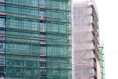 Σκάλα και υλικά σκαλωσιάς σε ένα εργοτάξιο οικοδομής, που καλύπτεται με το πλέγμα. Στοκ φωτογραφία με δικαίωμα ελεύθερης χρήσης