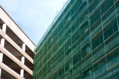 Σκάλα και υλικά σκαλωσιάς σε ένα εργοτάξιο οικοδομής, που καλύπτεται με το πλέγμα. Στοκ Φωτογραφίες