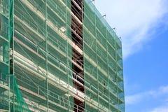 Σκάλα και υλικά σκαλωσιάς σε ένα εργοτάξιο οικοδομής, που καλύπτεται με το πλέγμα στο υπόβαθρο ουρανού. Στοκ φωτογραφία με δικαίωμα ελεύθερης χρήσης