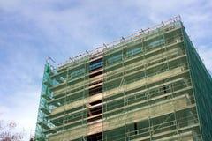 Σκάλα και υλικά σκαλωσιάς σε ένα εργοτάξιο οικοδομής, που καλύπτεται με το πλέγμα στο υπόβαθρο ουρανού. Στοκ εικόνα με δικαίωμα ελεύθερης χρήσης
