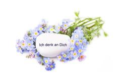 Σκέψη σας. Μπλε λουλούδια με την πέτρα και ένα γερμανικό κείμενο. Στοκ φωτογραφία με δικαίωμα ελεύθερης χρήσης