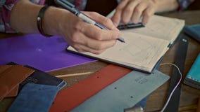Σκίτσο σχεδίων κατασκευαστών δέρματος στο σημειωματάριο Μικρή κατασκευή δέρματος απόθεμα βίντεο