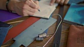 Σκίτσο σχεδίων κατασκευαστών δέρματος στο σημειωματάριο Σχεδιαστής προϊόντων που σύρει το νέο προϊόν απόθεμα βίντεο
