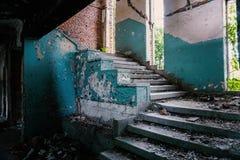 Σκαλοπάτια και σπασμένα παράθυρα σε ένα εγκαταλειμμένο, δυσαρεστημένο κτήριο στοκ φωτογραφίες